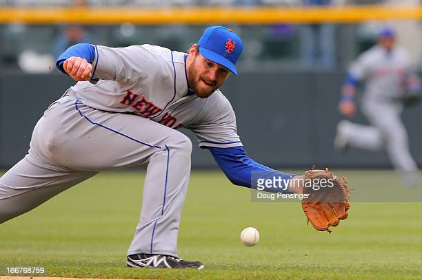 Second baseman Daniel Murphy of the New York Mets is unable to stop a single by Eric Young Jr of the Colorado Rockies in the fifth inning at Coors...