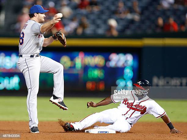 Second baseman Daniel Murphy of the New York Mets throws to first base over third baseman Adonis Garcia during the game at Turner Field on September...
