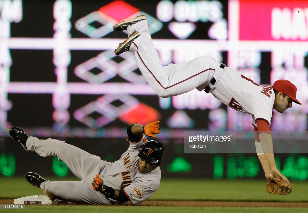 Second baseman Danny Espinosa of the Washington Nationals flips over Miguel Tejada of the San Francisco Giants after forcing him out at second base...