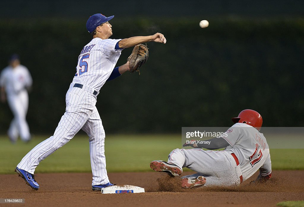 Second baseman <a gi-track='captionPersonalityLinkClicked' href=/galleries/search?phrase=Darwin+Barney&family=editorial&specificpeople=537975 ng-click='$event.stopPropagation()'>Darwin Barney</a> #15 of the Chicago Cubs (L) throws to first base to complete a double play after forcing out <a gi-track='captionPersonalityLinkClicked' href=/galleries/search?phrase=Shin-Soo+Choo&family=editorial&specificpeople=196543 ng-click='$event.stopPropagation()'>Shin-Soo Choo</a> #17 of the Cincinnati Reds at second base on a ground ball hit by Todd Frazier #21 during the third inning at Wrigley Field on August 12, 2013 in Chicago, Illinois.