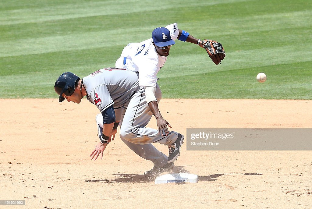 Second baseman <a gi-track='captionPersonalityLinkClicked' href=/galleries/search?phrase=Dee+Gordon&family=editorial&specificpeople=7091343 ng-click='$event.stopPropagation()'>Dee Gordon</a> #9 of the Los Angeles Dodgers collides with baserunner <a gi-track='captionPersonalityLinkClicked' href=/galleries/search?phrase=Yan+Gomes&family=editorial&specificpeople=9004037 ng-click='$event.stopPropagation()'>Yan Gomes</a> #10 of the Cleveland Indians after Gordon forced Gomes and threw to first in an unseccessful attempt to complete a double play in the sixth inning at Dodger Stadium on July 2, 2014 in Los Angeles, California.