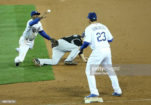 Second baseman Dee Gordon of the Los Angeles Dodgers flips the ball to first baseman Adrian Gonzalez to complete a double play after tagging out...