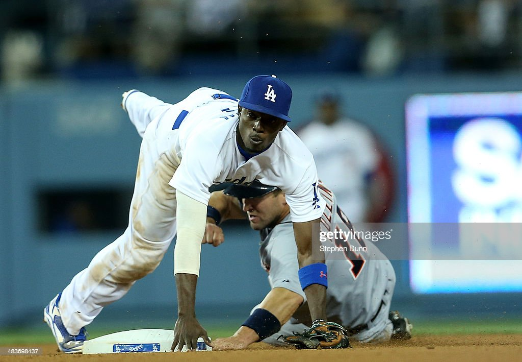 Second baseman <a gi-track='captionPersonalityLinkClicked' href=/galleries/search?phrase=Dee+Gordon&family=editorial&specificpeople=7091343 ng-click='$event.stopPropagation()'>Dee Gordon</a> #9 of the Los Angeles Dodgers watches as his throw to first to completes a double play after forcing out Tyler Collins #18 of the Detroit Tigers to end the top of the eighth inning at Dodger Stadium on April 9, 2014 in Los Angeles, California.