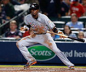 Second baseman Dee Gordon of the Miami Marlins attempts a drag bunt during the game against the Atlanta Braves at Turner Field on April 13 2015 in...