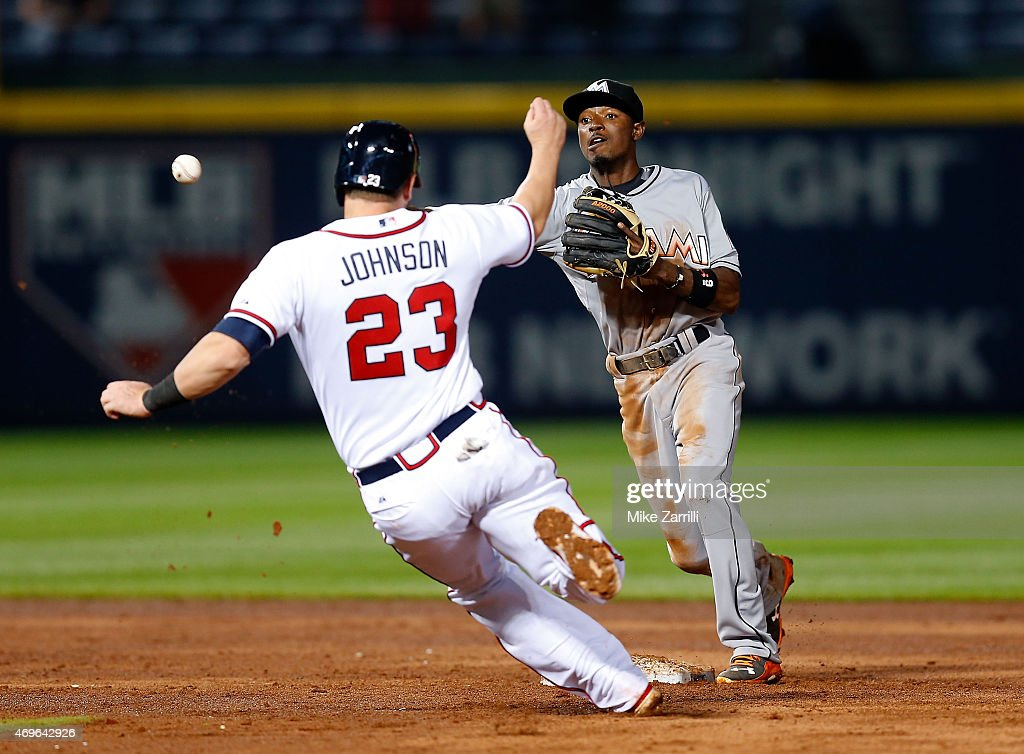 Second baseman Dee Gordon of the Miami Marlins throws to first base for a double play over Chris Johnson of the Atlanta Braves in the seventh inning...