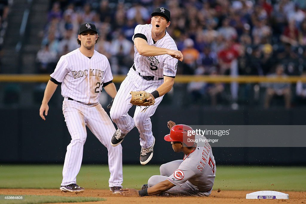 Second baseman <a gi-track='captionPersonalityLinkClicked' href=/galleries/search?phrase=DJ+LeMahieu&family=editorial&specificpeople=5940806 ng-click='$event.stopPropagation()'>DJ LeMahieu</a> #9 of the Colorado Rockies gets a force out on <a gi-track='captionPersonalityLinkClicked' href=/galleries/search?phrase=Ramon+Santiago&family=editorial&specificpeople=2984417 ng-click='$event.stopPropagation()'>Ramon Santiago</a> #7 of the Cincinnati Reds but is unable to turn the double play on Johnny Cueto #47 of the Cincinnati Reds in the fourth inning at Coors Field on August 15, 2014 in Denver, Colorado.