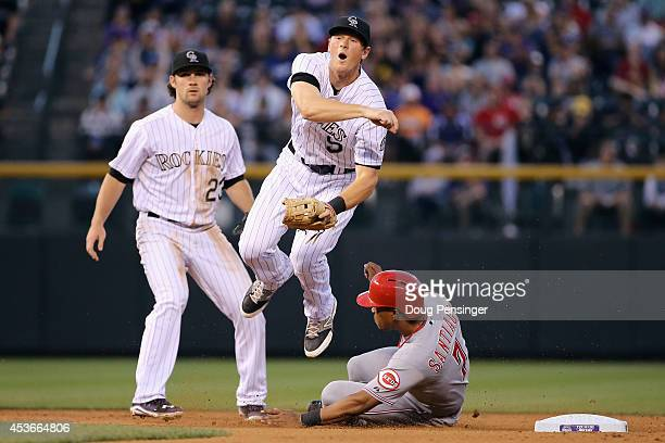 Second baseman DJ LeMahieu of the Colorado Rockies gets a force out on Ramon Santiago of the Cincinnati Reds but is unable to turn the double play on...