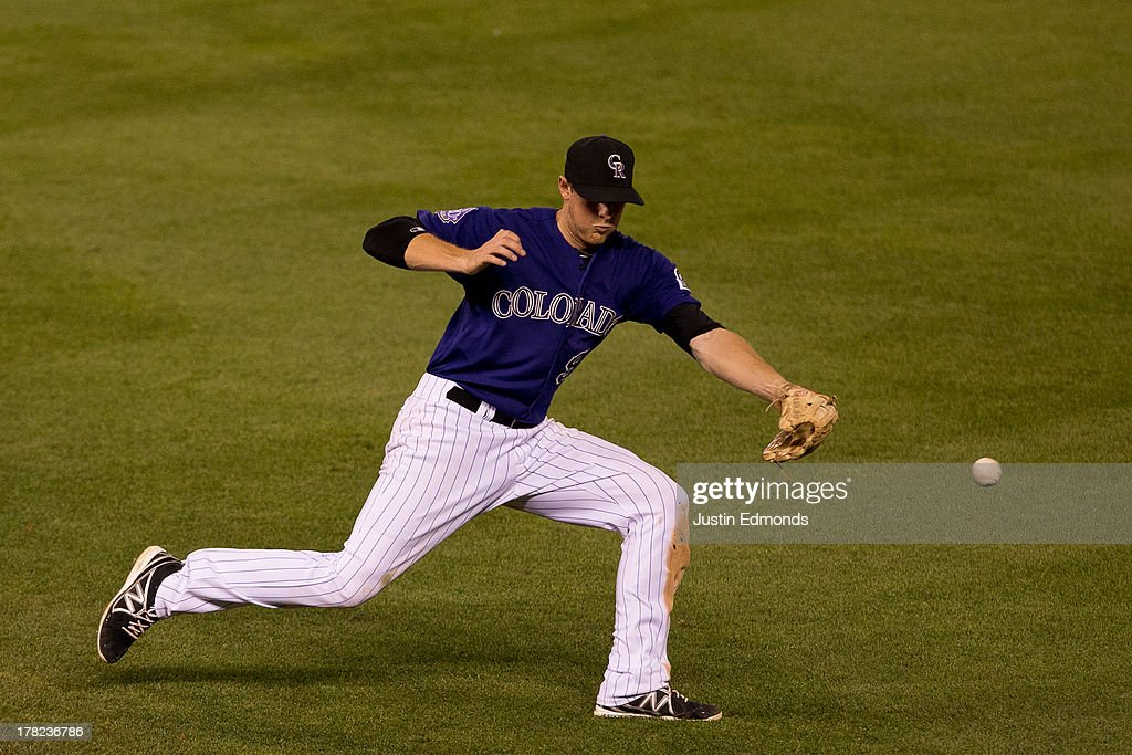 Second baseman DJ LeMahieu #9 of the Colorado Rockies is unable to knock down a base hit off the bat of Brandon Belt #9 of the San Francisco Giants during the sixth inning at Coors Field on August 27, 2013 in Denver, Colorado. The Giants defeated the Rockies 5-3.