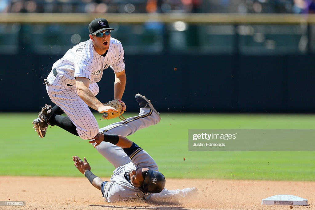 Second baseman <a gi-track='captionPersonalityLinkClicked' href=/galleries/search?phrase=DJ+LeMahieu&family=editorial&specificpeople=5940806 ng-click='$event.stopPropagation()'>DJ LeMahieu</a> #9 of the Colorado Rockies is upended after throwing to first base to complete the double play to end the seventh inning as Martin Maldonado #12 of the Milwaukee Brewers slides in late at Coors Field on June 20, 2015 in Denver, Colorado. The Rockies defeated the Brewers 5-1.