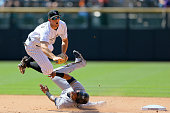 Second baseman DJ LeMahieu of the Colorado Rockies is upended after throwing to first base to complete the double play to end the seventh inning as...