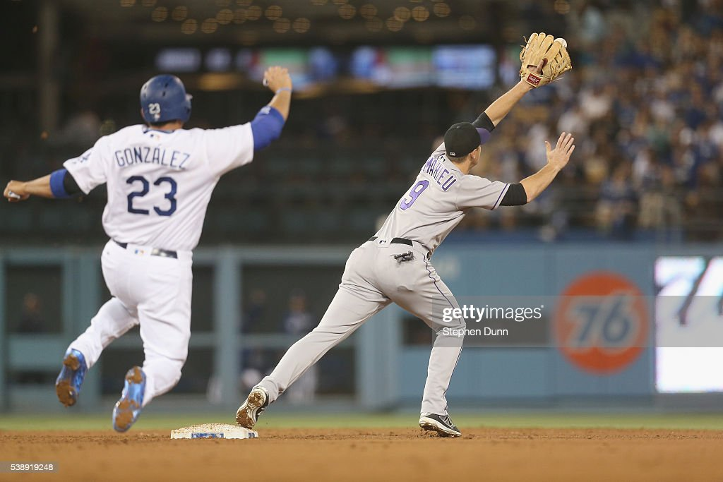 Second baseman DJ LeMahieu of the Colorado Rockies reaches for a throw to force out Adrian Gonzalez of the Los Angeles Dodgers for the final out of...