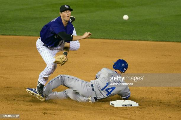 Second baseman DJ LeMahieu of the Colorado Rockies throws to first base to complete the double play as Mark Ellis of the Los Angeles Dodgers tries to...