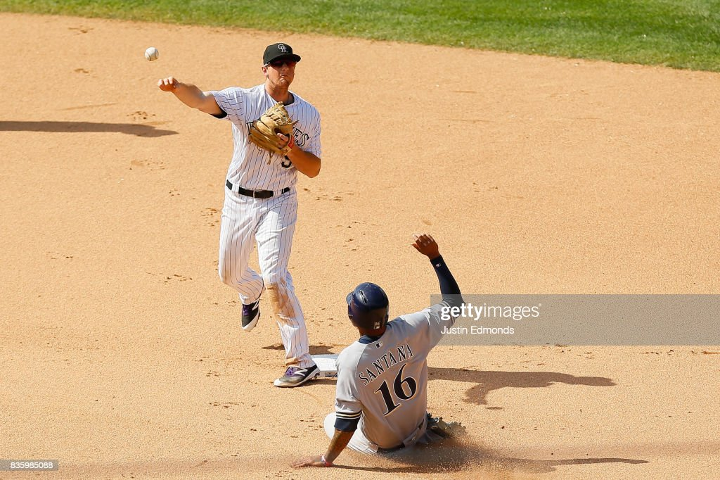 Second baseman DJ LeMahieu #9 of the Colorado Rockies throws to first base to complete the double play for the first two outs of the seventh inning as Domingo Santana #16 of the Milwaukee Brewers slides at Coors Field on August 20, 2017 in Denver, Colorado.