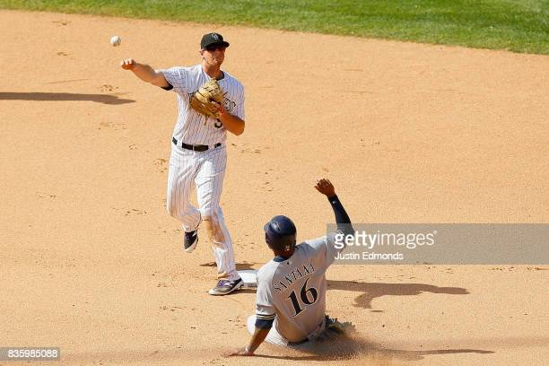 Second baseman DJ LeMahieu of the Colorado Rockies throws to first base to complete the double play for the first two outs of the seventh inning as...