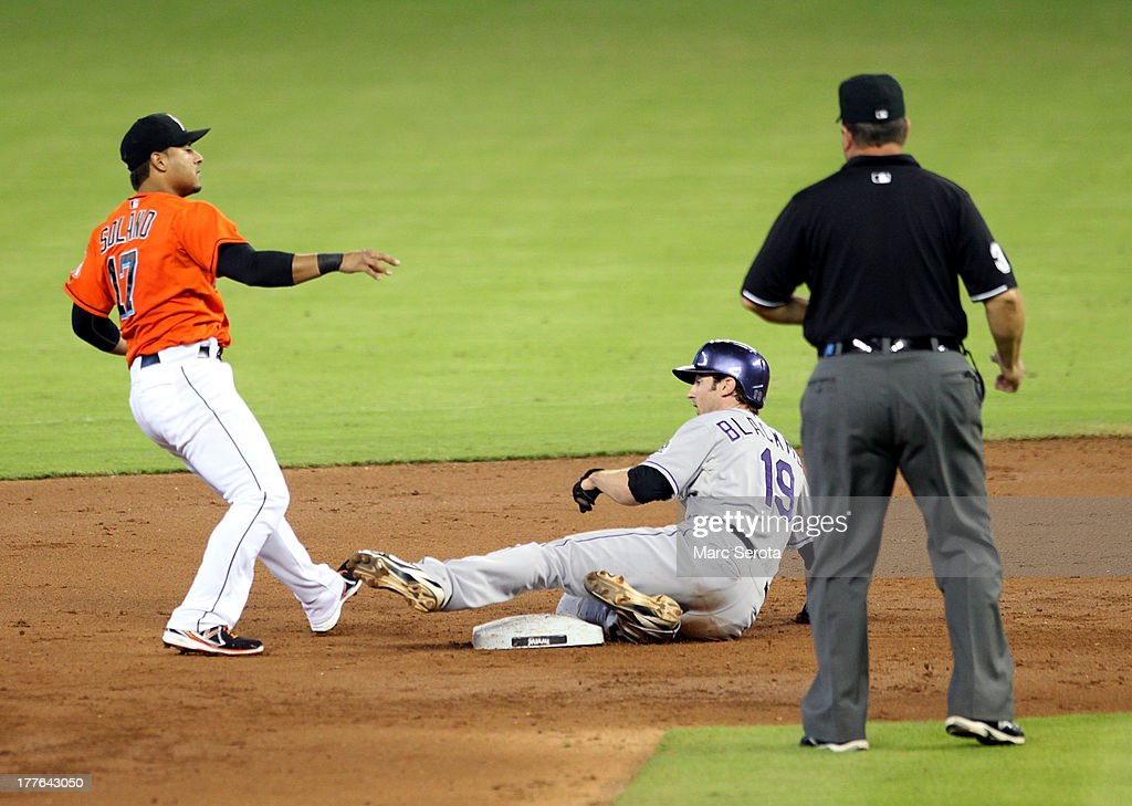 Second baseman Donovan Solano #17 of the Miami Marlins turns a double play against Charlie Blackmon #19 of the Colorado Rockies at Marlins Park on August 25, 2013 in Miami, Florida.