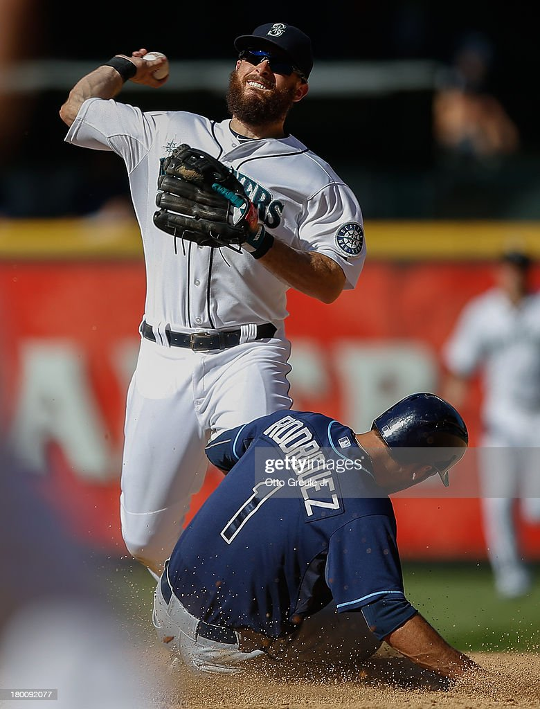 Second baseman <a gi-track='captionPersonalityLinkClicked' href=/galleries/search?phrase=Dustin+Ackley&family=editorial&specificpeople=4352278 ng-click='$event.stopPropagation()'>Dustin Ackley</a> #13 of the Seattle Mariners turns a double play over <a gi-track='captionPersonalityLinkClicked' href=/galleries/search?phrase=Sean+Rodriguez&family=editorial&specificpeople=4171805 ng-click='$event.stopPropagation()'>Sean Rodriguez</a> #1 of the Tampa Bay Rays to end the top of the eighth inning at Safeco Field on September 8, 2013 in Seattle, Washington.