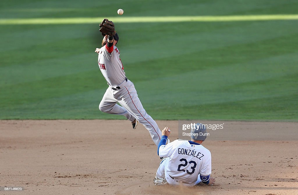 Second baseman Dustin Pedroia of the Boston Red Sox can't reach an errant throw on an attempt to force out Adrian Gonzalez of the Los Angeles Dodgers...