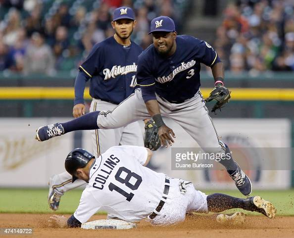 Second baseman Elian Herrera of the Milwaukee Brewers avoids Tyler Collins of the Detroit Tigers after turning the ball in an attempt to get a double...