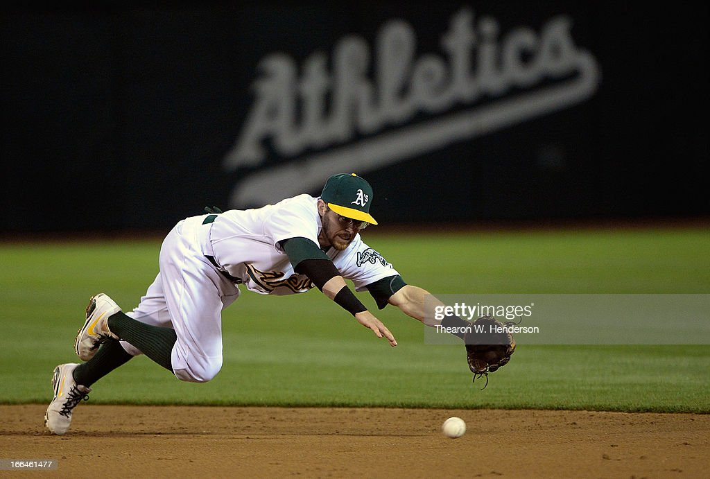 Second baseman <a gi-track='captionPersonalityLinkClicked' href=/galleries/search?phrase=Eric+Sogard&family=editorial&specificpeople=6796459 ng-click='$event.stopPropagation()'>Eric Sogard</a> #28 of the Oakland Athletics dives but misses the ball that goes for a base hit off the bat of Andy Dirks #12 of the Detroit Tigers in the third inning at O.co Coliseum on April 12, 2013 in Oakland, California.
