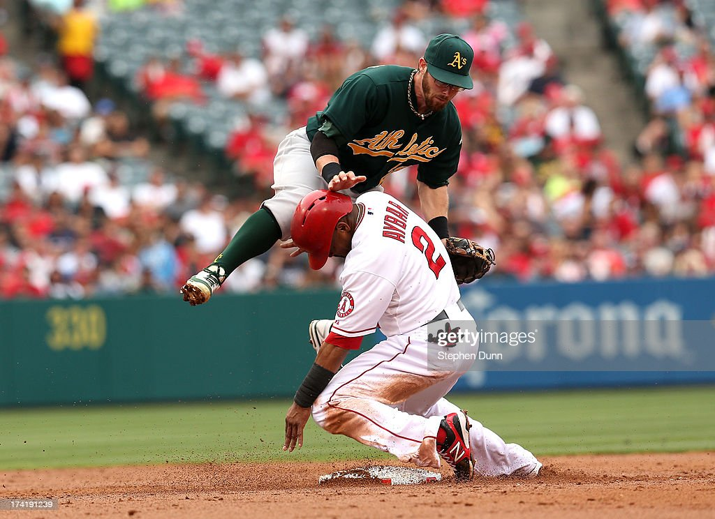Second baseman <a gi-track='captionPersonalityLinkClicked' href=/galleries/search?phrase=Eric+Sogard&family=editorial&specificpeople=6796459 ng-click='$event.stopPropagation()'>Eric Sogard</a> #28 of the Oakland Athletics gets tied up with Erik Aybar #2 of the Los Angeles Angels of Anaheim after forcing Aybar and turning a double play to end the third inning at Angel Stadium of Anaheim on July 21, 2013 in Anaheim, California.