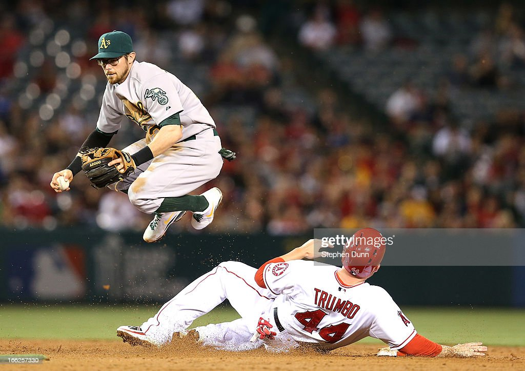 Second baseman Eric Sogard #28 of the Oakland Athletics jumps over Mark Trumbo #44 of the Los Angeles Angels of Anaheim after getting a force out in the third inning at Angel Stadium of Anaheim on April 10, 2013 in Anaheim, California.
