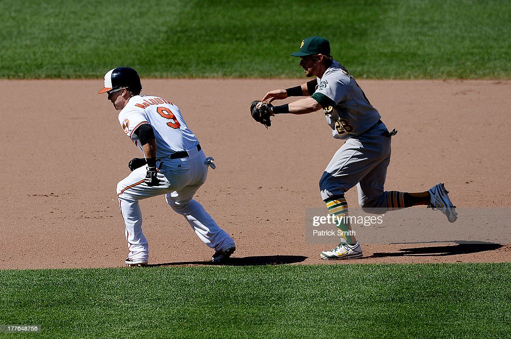 Second baseman <a gi-track='captionPersonalityLinkClicked' href=/galleries/search?phrase=Eric+Sogard&family=editorial&specificpeople=6796459 ng-click='$event.stopPropagation()'>Eric Sogard</a> #28 of the Oakland Athletics tags out base runner <a gi-track='captionPersonalityLinkClicked' href=/galleries/search?phrase=Nate+McLouth&family=editorial&specificpeople=536572 ng-click='$event.stopPropagation()'>Nate McLouth</a> #9 of the Baltimore Orioles during a rundown in the fourth inning at Oriole Park at Camden Yards on August 25, 2013 in Baltimore, Maryland. The Baltimore Orioles won, 10-3.