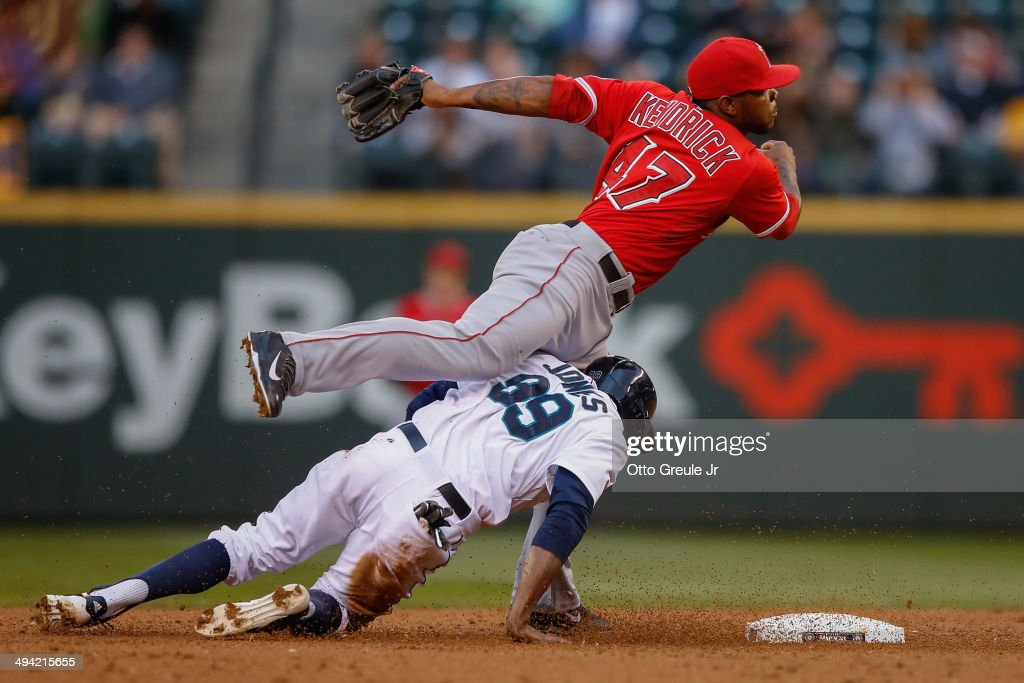 Second baseman Howie Kendrick of the Los Angeles Angels of Anaheim tries to turn a double play over James Jones of the Seattle Mariners in the third...