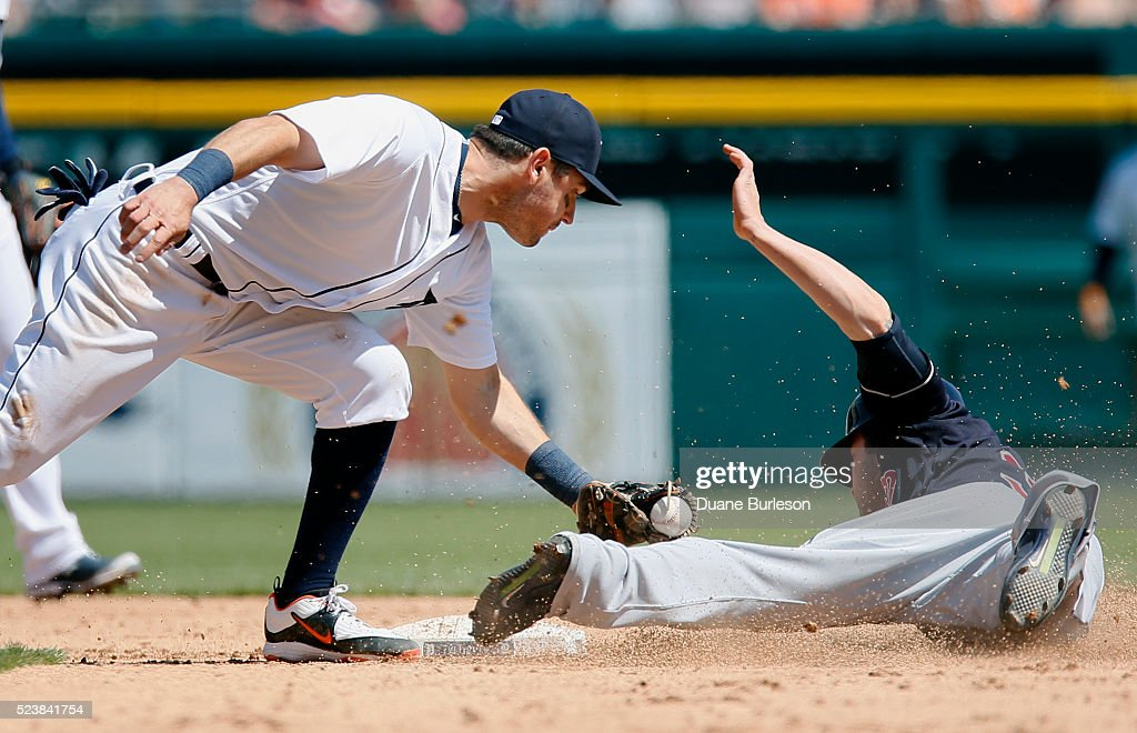 Second baseman Ian Kinsler of the Detroit Tigers hangs on to the ball to tag out Tyler Naquin of the Cleveland Indians trying to steal second base...