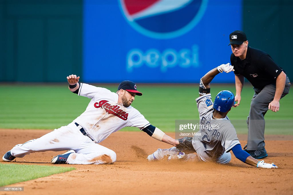 Second baseman <a gi-track='captionPersonalityLinkClicked' href=/galleries/search?phrase=Jason+Kipnis&family=editorial&specificpeople=5330784 ng-click='$event.stopPropagation()'>Jason Kipnis</a> #22 of the Cleveland Indians tries to tag <a gi-track='captionPersonalityLinkClicked' href=/galleries/search?phrase=Alcides+Escobar&family=editorial&specificpeople=4845889 ng-click='$event.stopPropagation()'>Alcides Escobar</a> #2 of the Kansas City Royals on a hit to left as second base umpire Tom Woodring #75 watches the play during the fifth inning at Progressive Field on July 27, 2015 in Cleveland, Ohio.