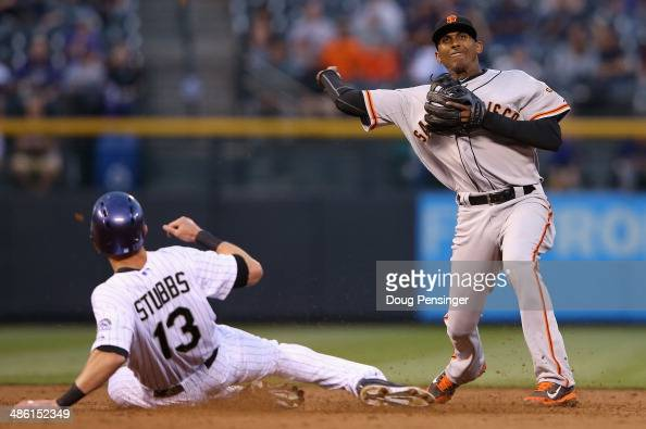 Second baseman Joaquin Arias of the San Francisco Giants turns a double play on Drew Stubbs of the Colorado Rockies to end the second inning at Coors...