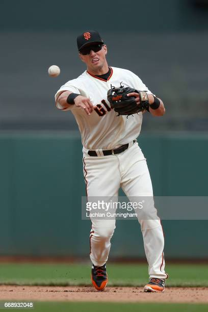 Second baseman Joe Panik of the San Francisco Giants fields the ball and throws to first base to get the out of Dustin Garneau of the Colorado...