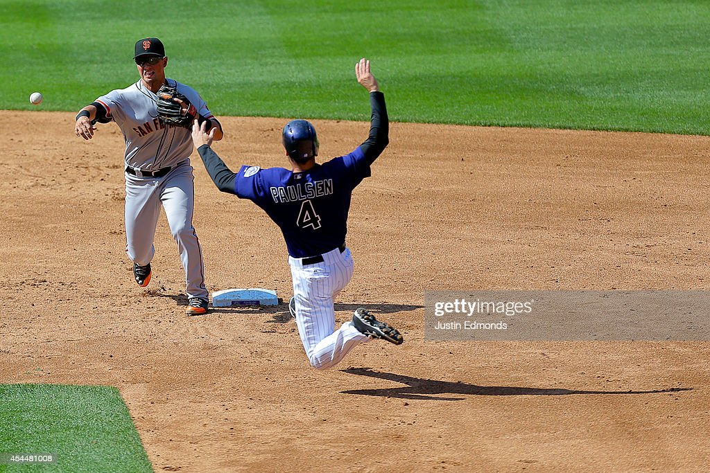 Second baseman <a gi-track='captionPersonalityLinkClicked' href=/galleries/search?phrase=Joe+Panik&family=editorial&specificpeople=9008902 ng-click='$event.stopPropagation()'>Joe Panik</a> #12 of the San Francisco Giants throws to first base to complete the double play for the first two outs of the ninth inning ahead of the slide from Ben Paulsen #4 of the Colorado Rockies at Coors Field on September 1, 2014 in Denver, Colorado. The teams were resuming a game previously suspended in the sixth inning on May 22 due to rain.