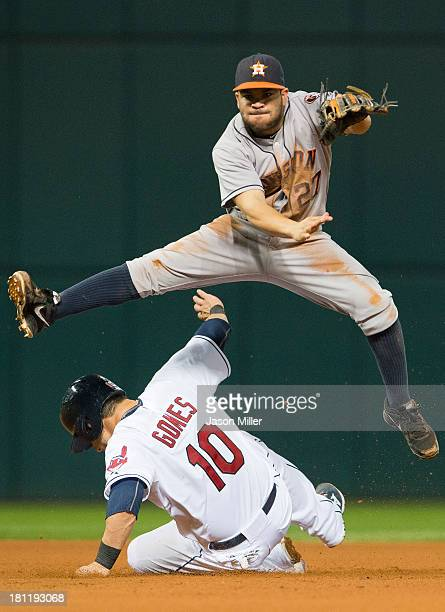 Second baseman Jose Altuve of the Houston Astros jumps over Yan Gomes of the Cleveland Indians after throwing to first during the fourth inning at...