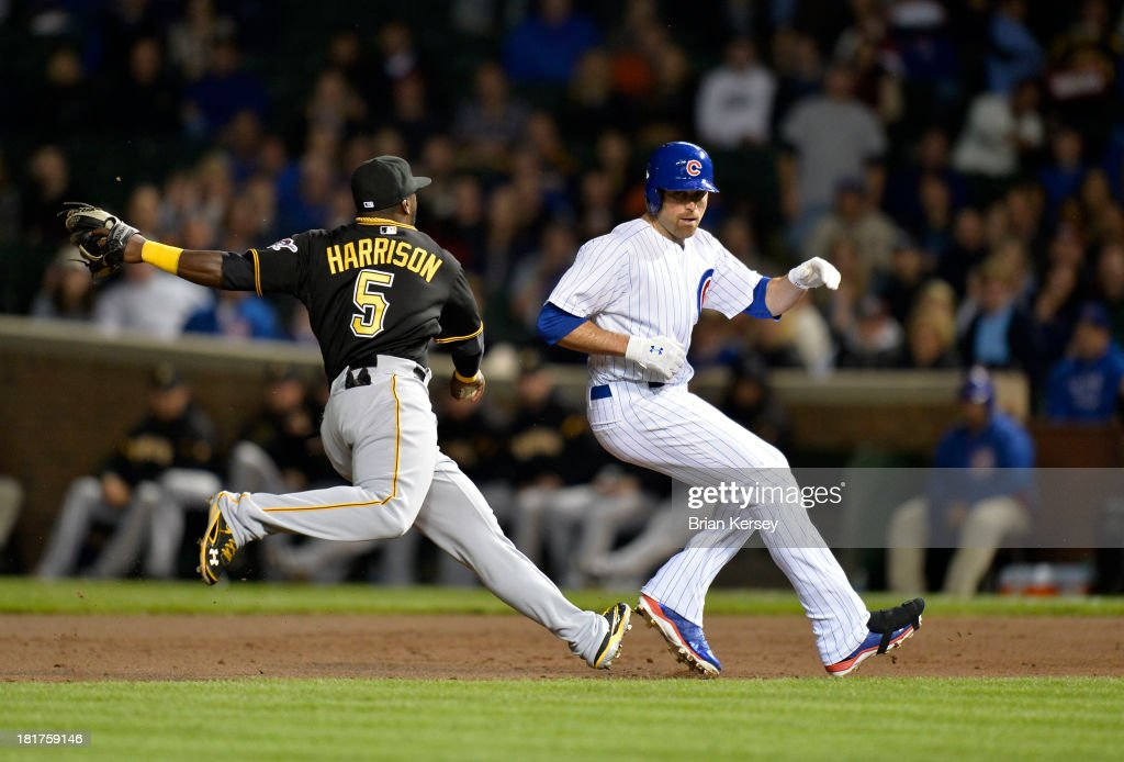 Second baseman Josh Harrison #5 of the Pittsburgh Pirates (L) chases down <a gi-track='captionPersonalityLinkClicked' href=/galleries/search?phrase=Nate+Schierholtz&family=editorial&specificpeople=803208 ng-click='$event.stopPropagation()'>Nate Schierholtz</a> #19 of the Chicago Cubs after he was caught trying to advance to second after hitting a single during the second inning at Wrigley Field on September 24, 2013 in Chicago, Illinois.