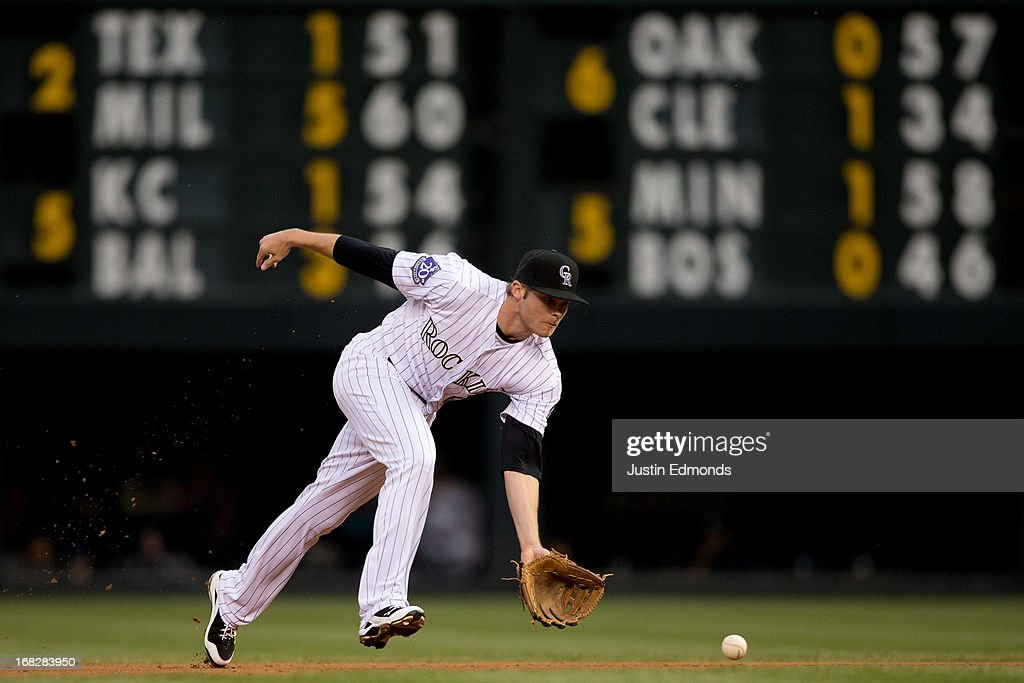 Second baseman <a gi-track='captionPersonalityLinkClicked' href=/galleries/search?phrase=Josh+Rutledge&family=editorial&specificpeople=9541486 ng-click='$event.stopPropagation()'>Josh Rutledge</a> #14 of the Colorado Rockies fields a ground ball on his way to recording the second out of the first inning against the New York Yankees at Coors Field on May 7, 2013 in Denver, Colorado.