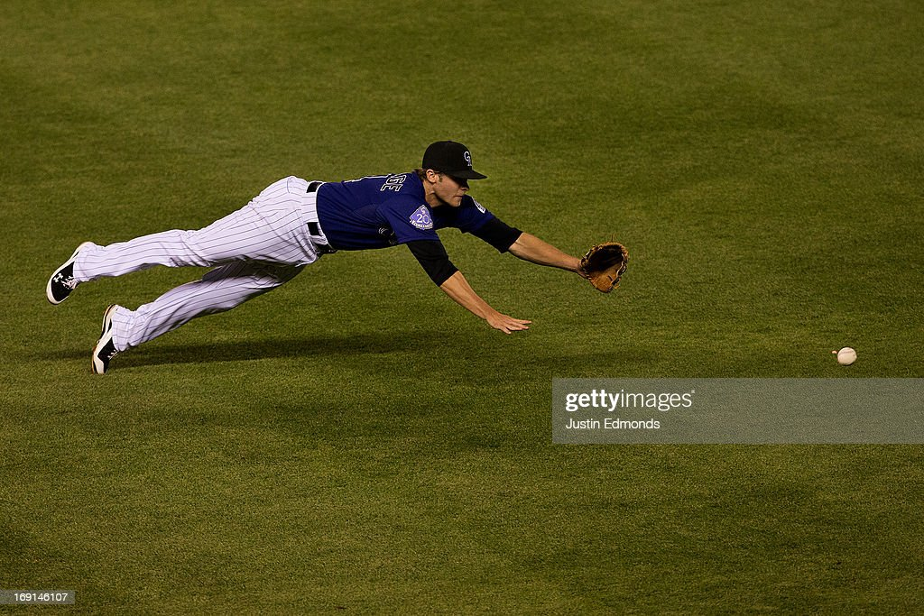 Second baseman <a gi-track='captionPersonalityLinkClicked' href=/galleries/search?phrase=Josh+Rutledge&family=editorial&specificpeople=9541486 ng-click='$event.stopPropagation()'>Josh Rutledge</a> #14 of the Colorado Rockies unsuccessfully dives for a base hit by Jason Kubel #13 of the Arizona Diamondbacks (not pictured) during the ninth inning at Coors Field on May 20, 2013 in Denver, Colorado. The Diamondbacks defeated the Rockies 5-1.