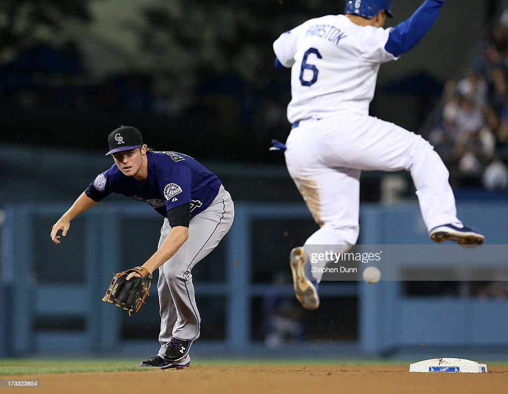 Second baseman Josh Rutlege #14 of the Colorado Rockies can't reach a throwing error by shortstop Troy Tulowitzki on a potential double play as <a gi-track='captionPersonalityLinkClicked' href=/galleries/search?phrase=Jerry+Hairston&family=editorial&specificpeople=213339 ng-click='$event.stopPropagation()'>Jerry Hairston</a> Jr. #6 jumps over the ball in the eighth inning at the Los Angeles Dodgers at Dodger Stadium on July 11, 2013 in Los Angeles, California.
