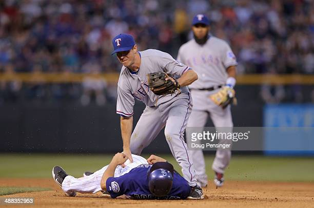 Second baseman Josh Wilson of the Texas Rangers tags out Nolan Arenado of the Colorado Rockies and turns a double play on the ground ball by Justin...