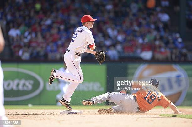 Second baseman Josh Wilson of the Texas Rangers throws to first base to complete a double play in the game against the Houston Astros at Globe Life...