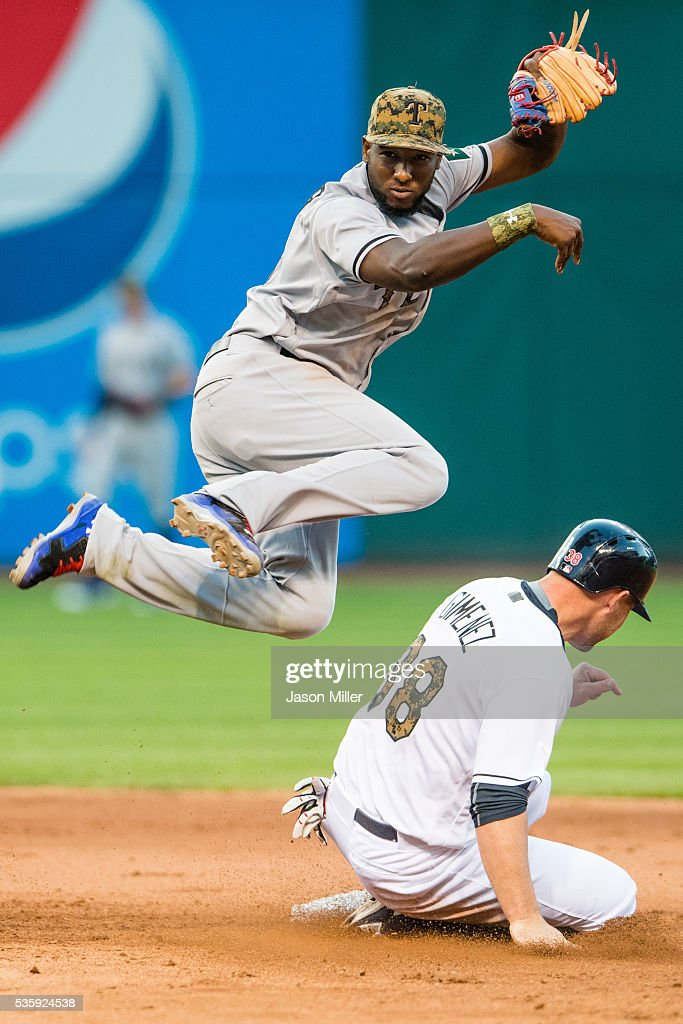 Second baseman <a gi-track='captionPersonalityLinkClicked' href=/galleries/search?phrase=Jurickson+Profar&family=editorial&specificpeople=2253684 ng-click='$event.stopPropagation()'>Jurickson Profar</a> #19 of the Texas Rangers throws out Carlos Santana #41 at first and <a gi-track='captionPersonalityLinkClicked' href=/galleries/search?phrase=Chris+Gimenez&family=editorial&specificpeople=4959066 ng-click='$event.stopPropagation()'>Chris Gimenez</a> #38 of the Cleveland Indians is out at second for a double play during the eighth inning at Progressive Field on May 30, 2016 in Cleveland, Ohio.