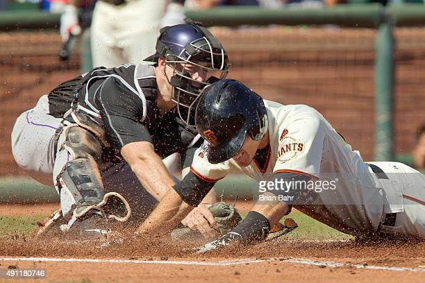 Second baseman Kelby Tomlinson of the San Francisco Giants dives across home plate against catcher Tom Murphy of the Colorado Rockies for an...