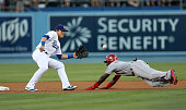 Second baseman Kike Hernandez of the Los Angeles Dodgers takes the throw before tagging out Brandon Phillips of the Cincinnati Reds attempting to...