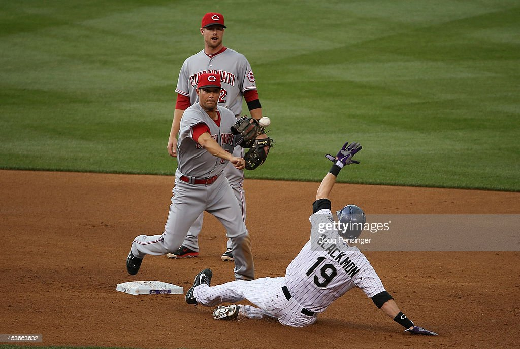 Second baseman Kris Negron #17 of the Cincinnati Reds turns a double play on Charlie Blackmon #19 of the Colorado Rockies on a ball hit by Justin Morneau #33 of the Colorado Rockies as shortstop Zack Cozart #2 of the Cincinnati Reds backs up the play to end the first inning at Coors Field on August 15, 2014 in Denver, Colorado.