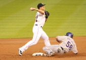 Second baseman Matt Dietrich of the Miami Marlins turns a double play against Jordan Pacheco of the Colorado Rockies at Marlins Park on April 2 2014...