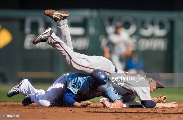 Second baseman Matt Tolbert of the Minnesota Twins falls on top of Mike Moustakas of the Kansas City Royals after throwing to first to complete a...