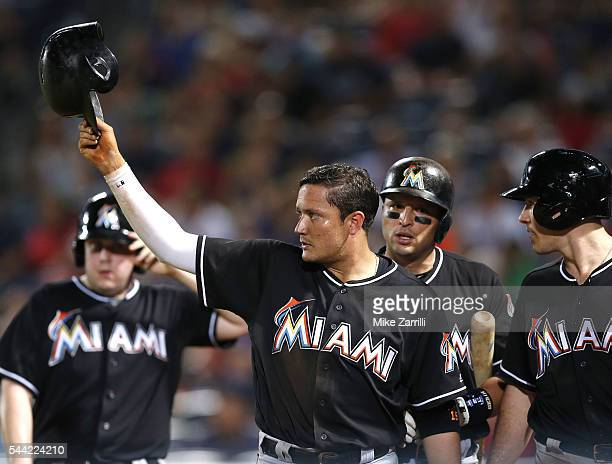 Second baseman Miguel Rojas of the Miami Marlins salutes pinch hitter Jose Fernandez after Fernandez's 2run goahead double in the twelfth inning...