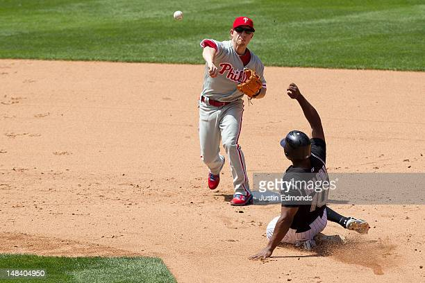 Second baseman Mike Fontenot of the Philadelphia Phillies throws to first base to complete the double play as Chris Nelson of the Colorado Rockies...
