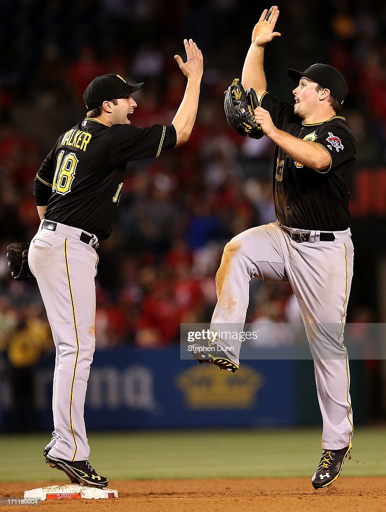 Second baseman Neil Walker #18 and right fielder <a gi-track='captionPersonalityLinkClicked' href=/galleries/search?phrase=Travis+Snider&family=editorial&specificpeople=4959427 ng-click='$event.stopPropagation()'>Travis Snider</a> #23 of the Pittsburgh Pirates celebrate after the game against the Los Angeles Angels of Anaheim at Angel Stadium of Anaheim on June 22, 2013 in Anaheim, California. The Pirates won 6-1.