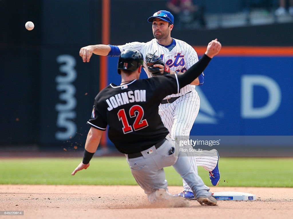 Second baseman Neil Walker of the New York Mets gets the force out on Chris Johnson of the Miami Marlins and throws to first to get Ichiro Suzuki for...