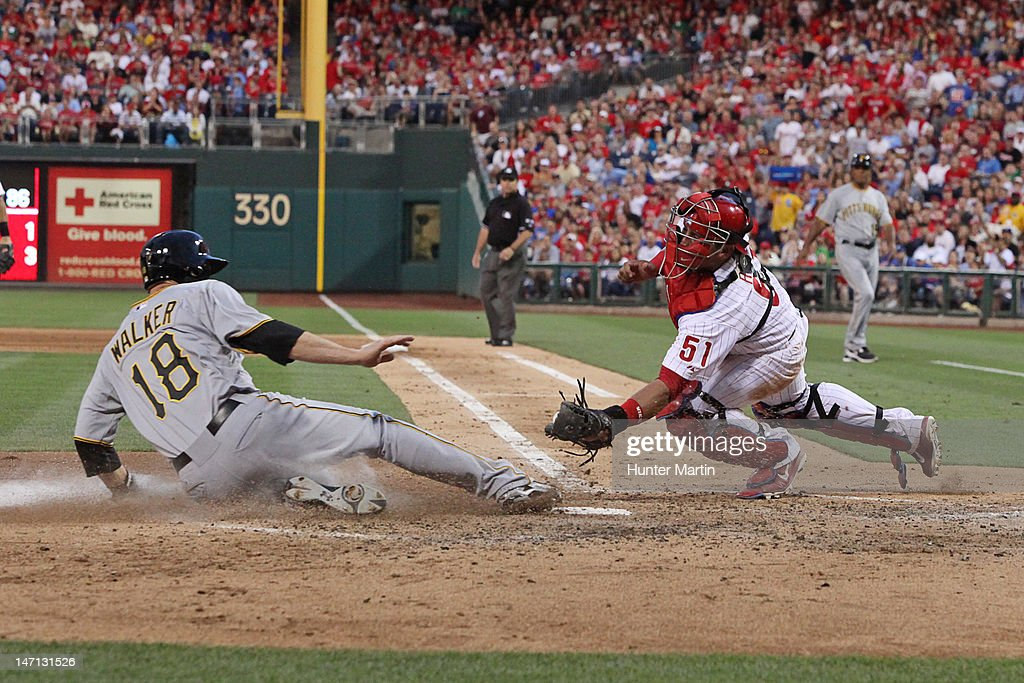 Second baseman Neil Walker #18 of the Pittsburgh Pirates slides under the tag of catcher Carlos Ruiz #51 of the Philadelphia Phillies during a game at Citizens Bank Park on June 25, 2012 in Philadelphia, Pennsylvania.